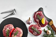 Fresh raw beef steaks with herbs, garlic, olive oil, pepper, salt and rosemary on black board: Tenderloin, Striploin. Rib Eye and a kitchen ax on white Royalty Free Stock Photo