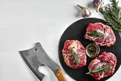 Fresh raw beef steaks with herbs, garlic, olive oil, pepper, salt and rosemary on black board: Tenderloin, Striploin. Rib Eye and a kitchen ax on white Royalty Free Stock Image