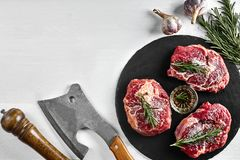 Fresh raw beef steaks with herbs, garlic, olive oil, pepper, salt and rosemary on black board: Tenderloin, Striploin. Rib Eye and a kitchen ax on white Royalty Free Stock Images
