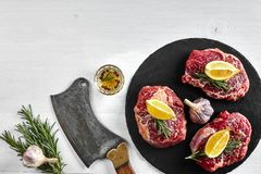 Fresh raw beef steaks with herbs, garlic, olive oil, pepper, salt and rosemary on black board: Tenderloin, Striploin. Rib Eye and a kitchen ax on white Stock Image