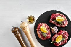 Fresh raw beef steaks with herbs, garlic, olive oil, pepper, salt and rosemary on black board: Tenderloin, Striploin. Rib Eye on white background. Top view Stock Photography