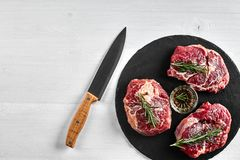 Fresh raw beef steaks with herbs, garlic, olive oil, pepper, salt and rosemary on black board: Tenderloin, Striploin. Rib Eye on white background. Top view Royalty Free Stock Photography