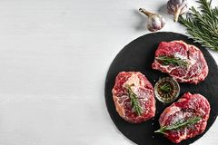 Fresh raw beef steaks with herbs, garlic, olive oil, pepper, salt and rosemary on black board: Tenderloin, Striploin. Rib Eye on white background. Top view Stock Photo