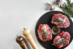 Fresh raw beef steaks with herbs, garlic, olive oil, pepper, salt and rosemary on black board: Tenderloin, Striploin. Rib Eye on white background. Top view Stock Image