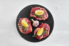 Fresh raw beef steaks with herbs, garlic, olive oil, pepper, salt and rosemary on black board: Tenderloin, Striploin. Rib Eye on white background. Top view Stock Images