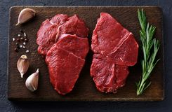 Fresh raw beef steaks, pepper, garlic, salt and rosemary. On a dark wooden background. Flat lay Stock Photography