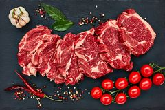 Fresh raw beef steaks with pepper and tomatoes on black slate board. Copy space. Top view Royalty Free Stock Image