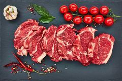 Fresh raw beef steaks with pepper and tomatoes on black slate board. Copy space, top view Royalty Free Stock Photo