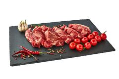 Fresh raw beef steaks with pepper and tomatoes on black slate board. Isolated. Over white Royalty Free Stock Image
