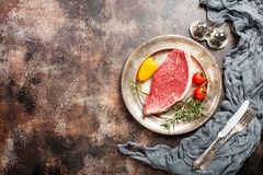 Fresh raw beef steaks. Fresh raw Prime Black Angus beef strip steaks on metal plate over dark rustic concrete background, top view. Ingredients set for making Stock Photography