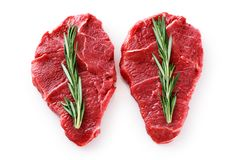Fresh raw beef steaks and rosemary isolated on white background. With clipping path Stock Photo
