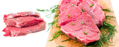 Fresh and raw beef steaks in white background. Fresh  raw beef steaks in white background and wooden board Stock Images