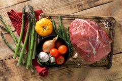 Fresh raw beef tenderloin with different vegetables on wooden ta. Ble, top view. Ingredients for cooking healthy food Royalty Free Stock Photos