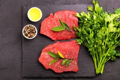 Fresh raw beef tenderloin and marbled steaks with seasoning. Fresh raw beef tenderloin and marbled steaks on slate black plate with seasoning. Top view Royalty Free Stock Photo