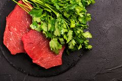 Fresh raw beef tenderloin and marbled steaks with seasoning. Fresh raw beef tenderloin and marbled steaks on slate black plate with seasoning. Top view Royalty Free Stock Image