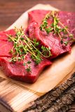 Fresh raw beef tenderloin and marbled steaks with seasoning. Fresh raw beef tenderloin and marbled steaks on wooden cutting board with seasoning. Top view Royalty Free Stock Photos