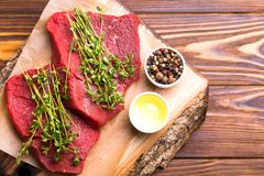 Fresh raw beef tenderloin and marbled steaks with seasoning. Fresh raw beef tenderloin and marbled steaks on wooden cutting board with seasoning. Top view Stock Photo