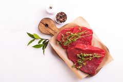 Fresh raw beef tenderloin and marbled steaks with seasoning. Fresh raw beef tenderloin and marbled steaks on wooden cutting board with seasoning. Top view Royalty Free Stock Photography