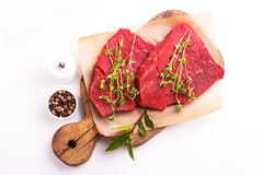 Fresh raw beef tenderloin and marbled steaks with seasoning. Fresh raw beef tenderloin and marbled steaks on wooden cutting board with seasoning. Top view Stock Images