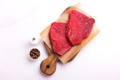 Fresh raw beef tenderloin and marbled steaks with seasoning. Fresh raw beef tenderloin and marbled steaks on wooden cutting board with seasoning. Top view Stock Photos