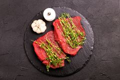 Fresh raw beef tenderloin and marbled steaks with seasoning. Fresh raw beef tenderloin and marbled steaks on slate black plate with seasoning. Top view Stock Images