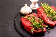 Fresh raw beef tenderloin and marbled steaks with seasoning. Fresh raw beef tenderloin and marbled steaks on slate black plate with seasoning. Top view Royalty Free Stock Photos