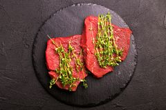 Fresh raw beef tenderloin and marbled steaks with seasoning. Fresh raw beef tenderloin and marbled steaks on slate black plate with seasoning. Top view Stock Photos