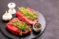 Fresh raw beef tenderloin and marbled steaks with seasoning. Fresh raw beef tenderloin and marbled steaks on slate black plate with seasoning. Top view Stock Photo