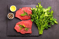 Fresh raw beef tenderloin and marbled steaks with seasoning. Fresh raw beef tenderloin and marbled steaks on slate black plate with seasoning. Top view Stock Photography