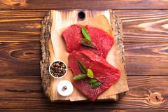 Fresh raw beef tenderloin and marbled steaks with seasoning. Fresh raw beef tenderloin and marbled steaks on wooden cutting board with seasoning. Top view Royalty Free Stock Photo