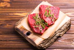 Fresh raw beef tenderloin and marbled steaks with seasoning. Fresh raw beef tenderloin and marbled steaks on wooden cutting board with seasoning. Top view Stock Photography