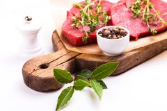 Fresh raw beef tenderloin and marbled steaks with seasoning. Fresh raw beef tenderloin and marbled steaks on wooden cutting board with seasoning. Top view Stock Image
