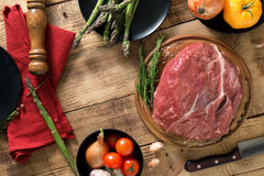 Fresh raw beef tenderloin with vegetables on wooden table. Fresh raw beef tenderloin with vegetables on a wooden table, top view. Ingredients for cooking healthy Stock Photos