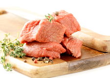 Fresh raw beef with thyme and spices. On a cutting board Royalty Free Stock Photography