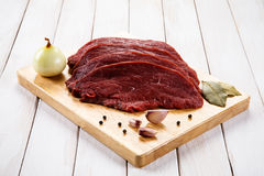 Fresh raw beef. Fresh beef and vegetables on wooden cutting board Stock Images