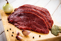 Fresh raw beef. Fresh beef and vegetables on wooden cutting board Stock Image