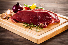 Fresh raw beef. Fresh beef and vegetables on wooden cutting board Royalty Free Stock Photography