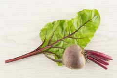 Fresh raw Beetroot isolated on grey wood. Red beet young bulb and one green leaf flatlay isolated on grey wood background top view Stock Photo