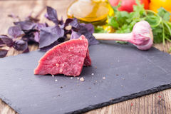 Fresh raw beef with vegetables. Fresh raw beef fillet with vegetables on background Royalty Free Stock Photo