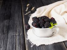 Fresh raw blackberries in metal cup, selective focus. Fresh raw ripe blackberries in a metal cup on black wooden table, selective focus, space for text Stock Photo