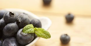 Fresh and raw blueberries on wooden background. Berries lieing on nice old table with leaf of mint Stock Image