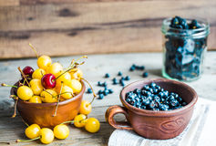 Fresh raw blueberry, yellow cherry and mulberry  on gray wooden. Fresh raw blueberry, yellow cherry and mulberry on gray wooden background, assorted summer Stock Images