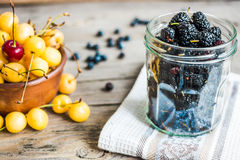 Fresh raw blueberry, yellow cherry and mulberry  on gray wooden. Fresh raw blueberry, yellow cherry and mulberry on gray wooden background, assorted summer Stock Photo