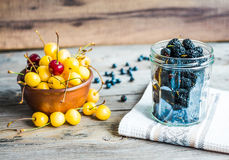 Fresh raw blueberry, yellow cherry and mulberry  on gray wooden. Fresh raw blueberry, yellow cherry and mulberry on gray wooden background, assorted summer Royalty Free Stock Image