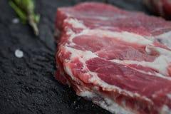 Fresh raw boneless pork neck slices on black stone background. Top view. royalty free stock photos
