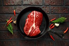 Fresh Raw braising steak in rustic skillet with rosemary, chilli and garlic.  Royalty Free Stock Photo