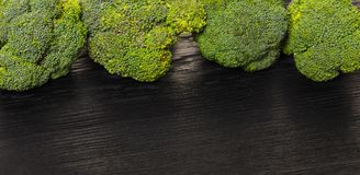 Fresh raw broccoli. On a black wooden background Royalty Free Stock Images