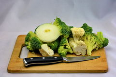 Fresh Raw Broccoli and Cauliflower Stir Fry. Ingredients with raw onion slice.  Presented on wooden cutting board with knife.  Plain white background Stock Image