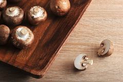 Fresh raw brown chestnut mushrooms whole in square wooden plate Royalty Free Stock Photography