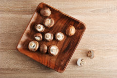 Fresh raw brown chestnut mushrooms whole in square wooden plate Royalty Free Stock Image